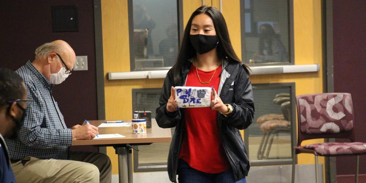 Student showing her mask artwork
